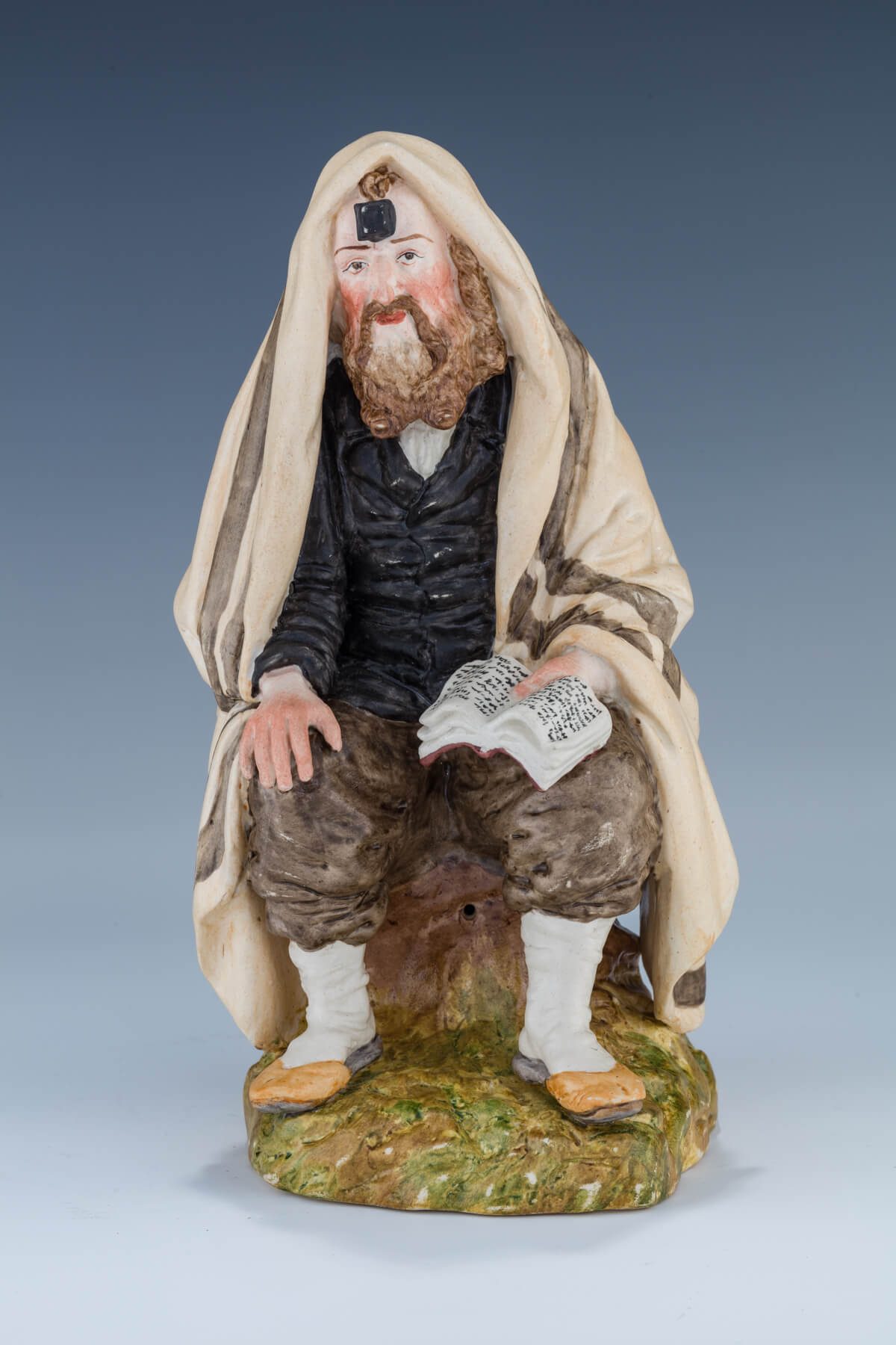 18. A Porcelain Figurine Of A Seated Hasidic Man In Prayer