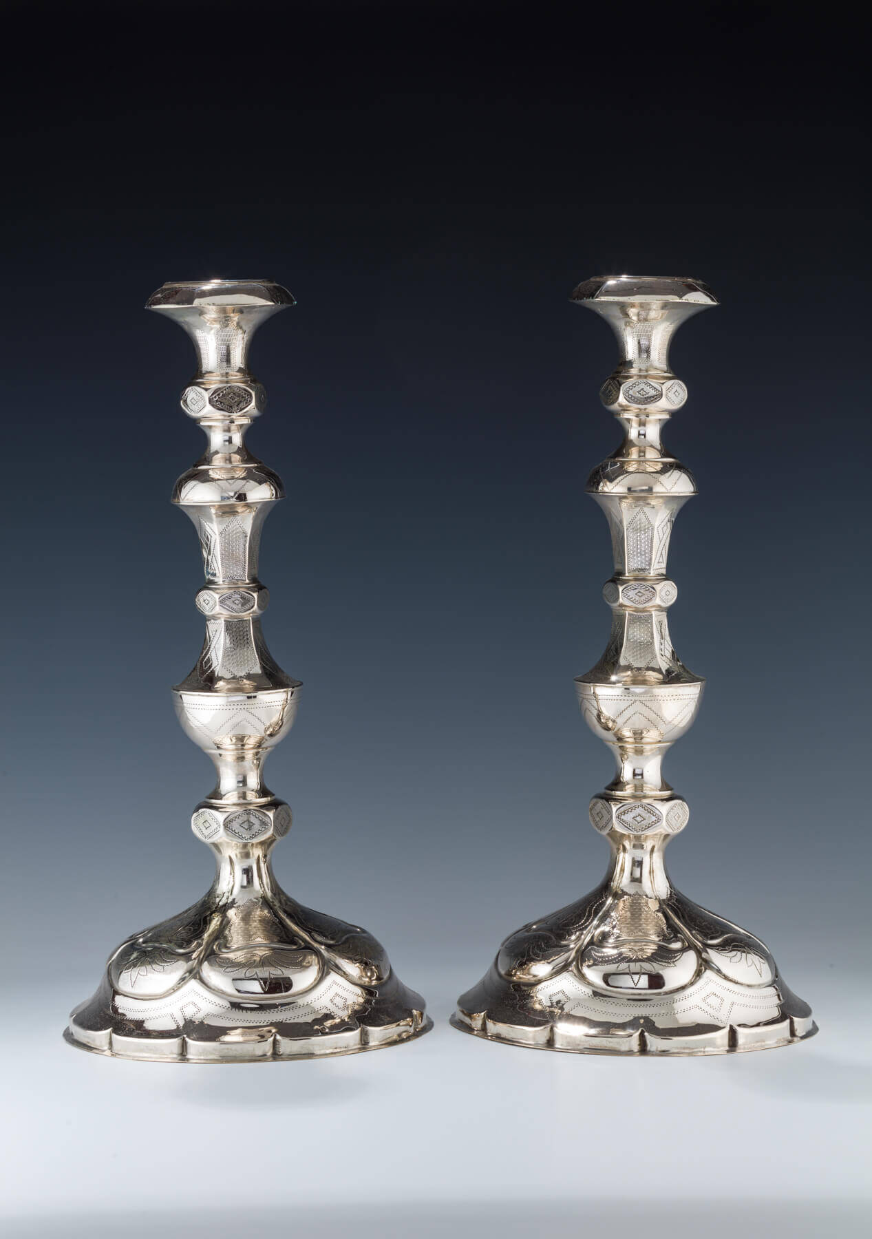 043. A PAIR OF LARGE SILVER CANDLESTICKS