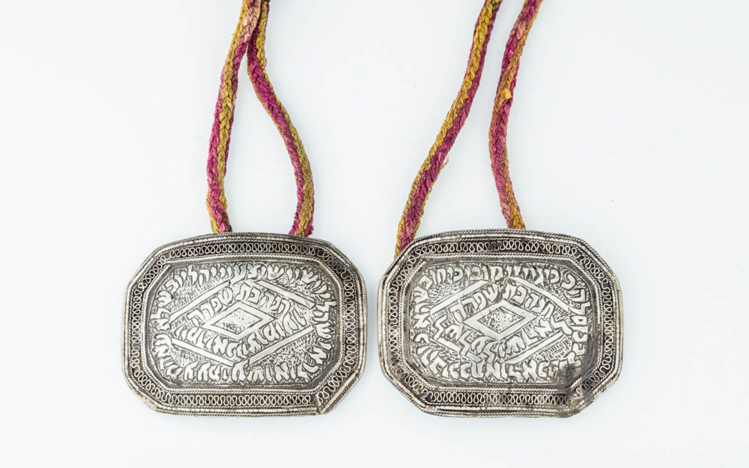 009. A PAIR OF SILVER AMULETS