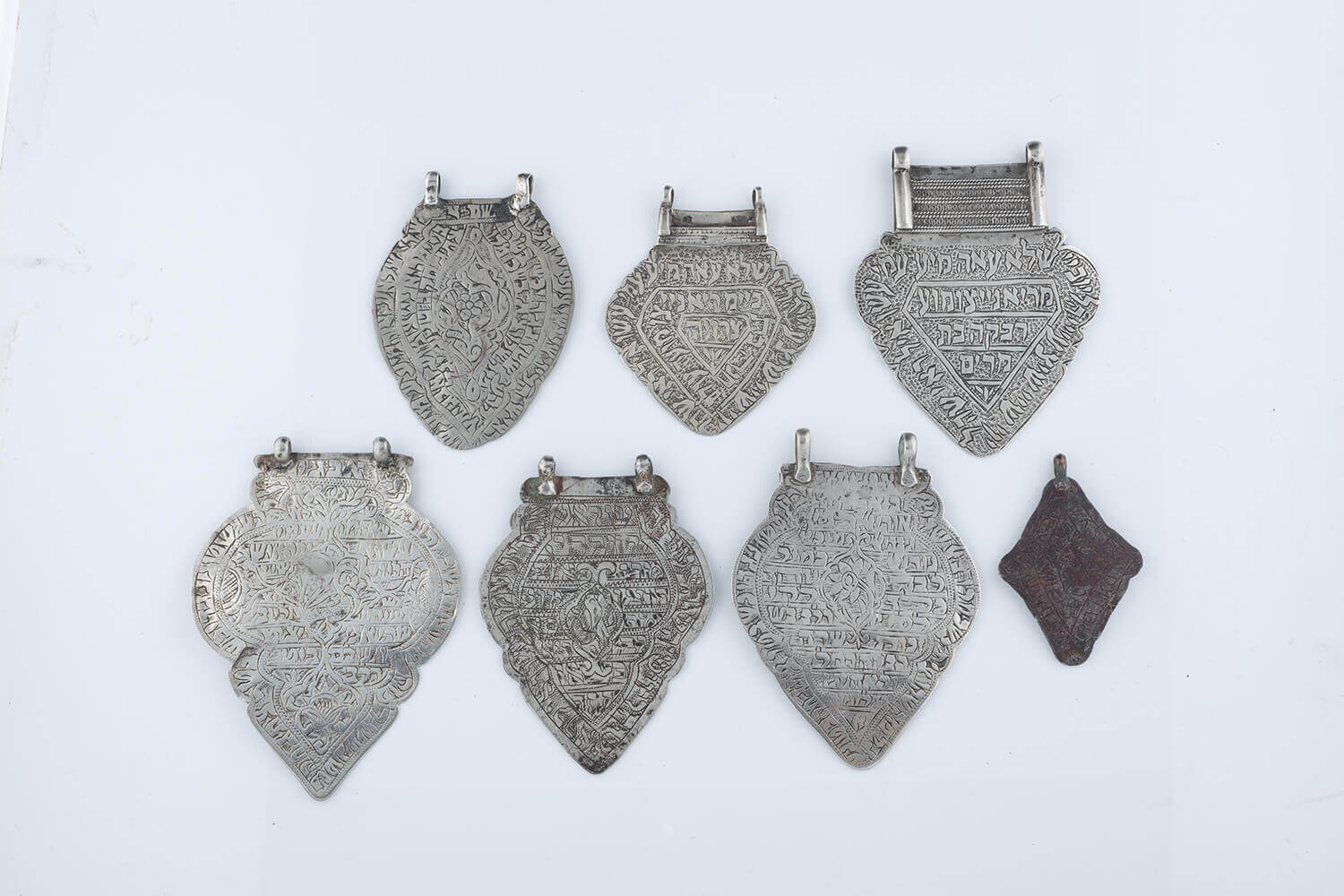 029. A GROUP OF SEVEN HEART SHAPED AMULETS