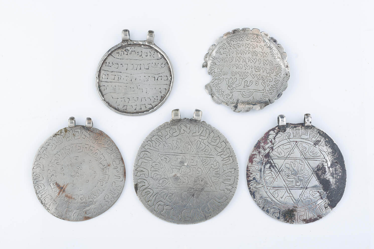 030. A GROUP OF FIVE LARGE CIRCULAR AMULETS