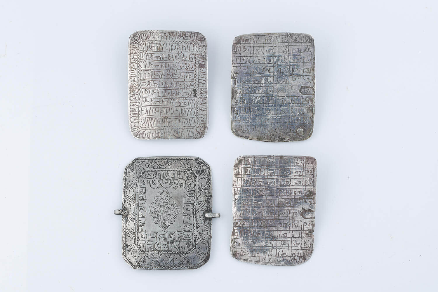 028. A GROUP OF FOUR SILVER SQUARE AMULETS